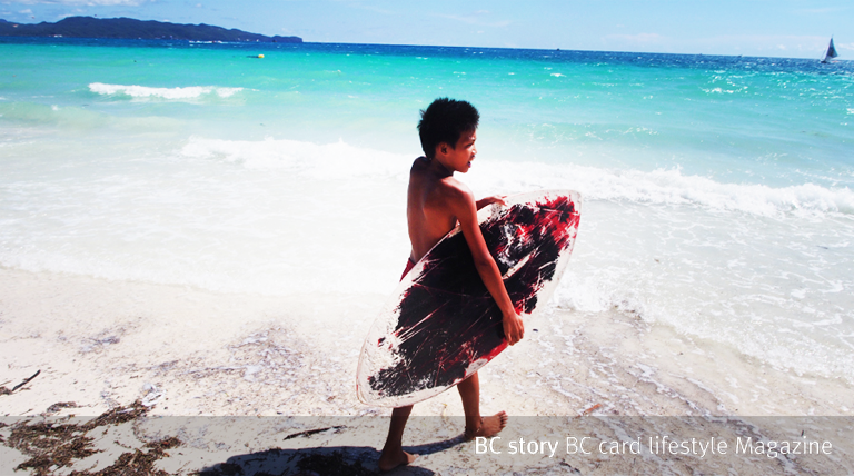 서핑보드를 들고가는 외국인 어린이